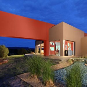 This is a look at the back of the house showing a large bright orange structure connected to the earthy walls of the house with large glass walls at the base. You can also see the landscaping with walkways and shrubs. Image courtesy of Toptenrealestatedeals.com.