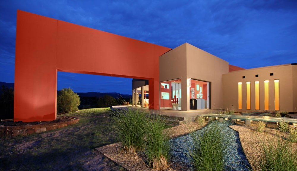 This is a look at the back of the house showing a large bright orange structure connected to the earthy walls of the house with large glass walls at the base. You can also see the landscaping with walkways and shrubs.