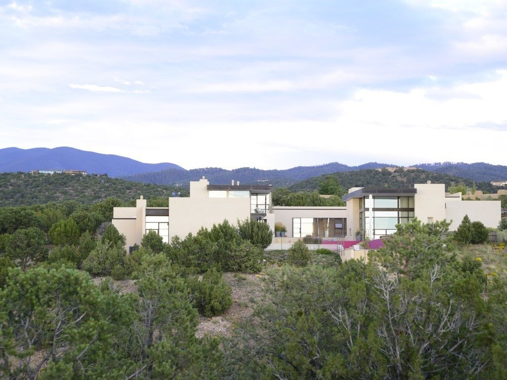 This is an aerial view of the house showing the bright exterior walls along with glass walls that makes the house stand out against the surrounding landscape. Image courtesy of Toptenrealestatedeals.com.