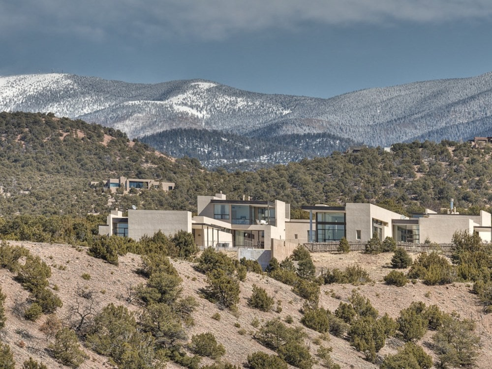 This is an aerial view of the contemporary house that is perched on hill surrounded by a landscape of shrubs. Image courtesy of Toptenrealestatedeals.com.