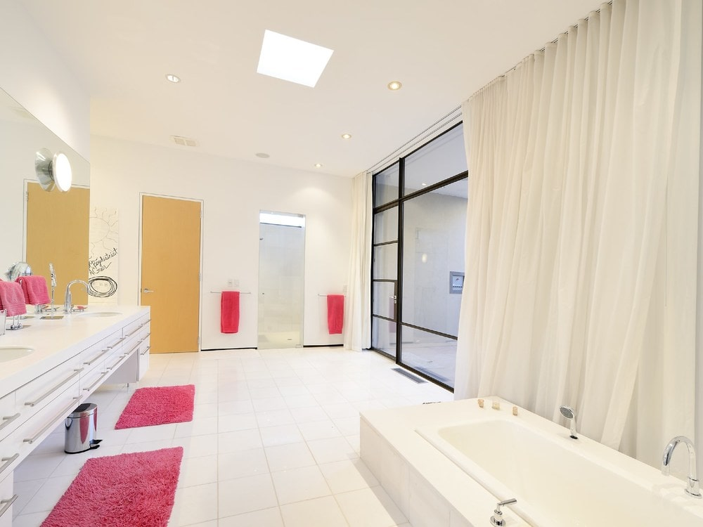 The bathroom has light and bright hues on its floor, walls and ceiling as well as the bathtub and vanity. These are complemented by the pink accents of the area rugs and towels. Image courtesy of Toptenrealestatedeals.com.