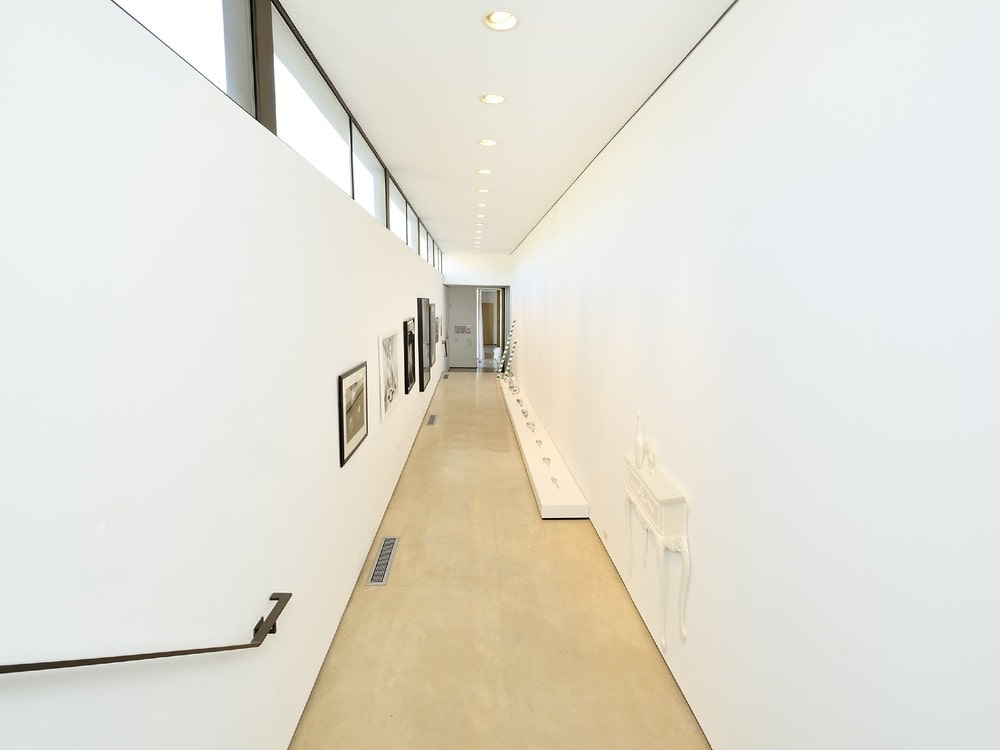 This is a look at the hallway of the house with bright white walls on both sides of the long and narrow light hardwood flooring. Image courtesy of Toptenrealestatedeals.com.