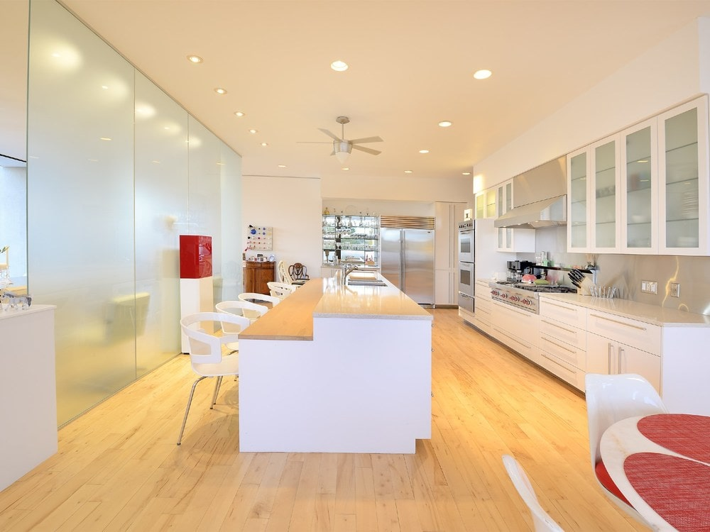 The kitchen has light hardwood flooring that matches the countertop of the kitchen island. These are paired well with the white cabinetry and white ceiling. Image courtesy of Toptenrealestatedeals.com.