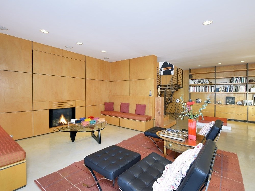 This living room has a fireplace embedded into the wooden wall on the far side across from the black leather chairs and glass coffee table. . Image courtesy of Toptenrealestatedeals.com.