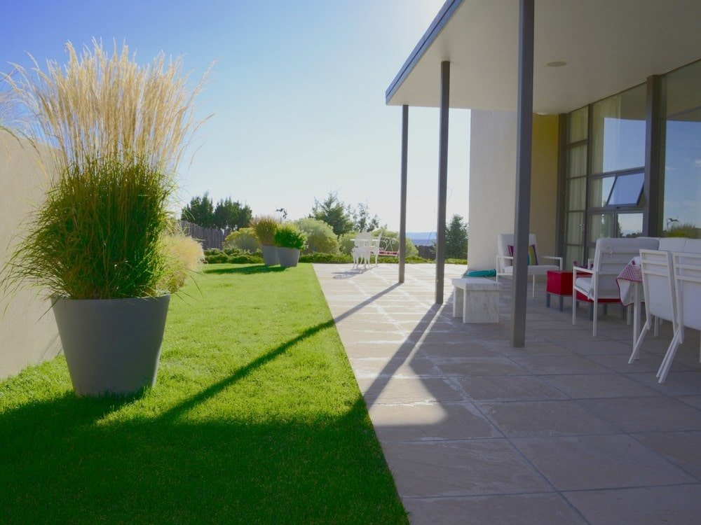 This is a look at the patio of the house with concrete flooring and thin pillars before transitioning to the grass lawn adorned with potted plants. Image courtesy of Toptenrealestatedeals.com.
