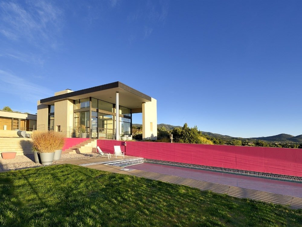 This is a look at the contemporary house with large glass walls and beige pillars. You can also see here the long hot-pink wall beside the pool of the backyard. Image courtesy of Toptenrealestatedeals.com.