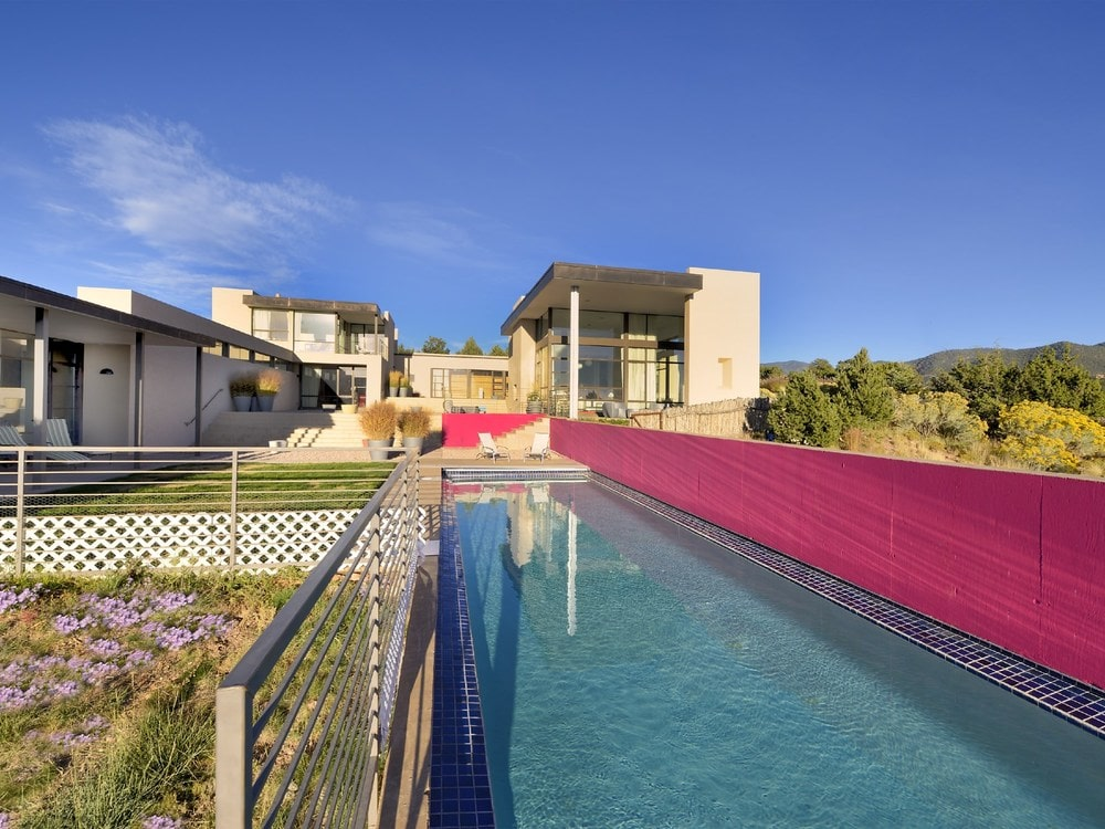 This is the backyard pool with a long hot-pink wall that stands out against the earthy tones of the contemporary home. Image courtesy of Toptenrealestatedeals.com.