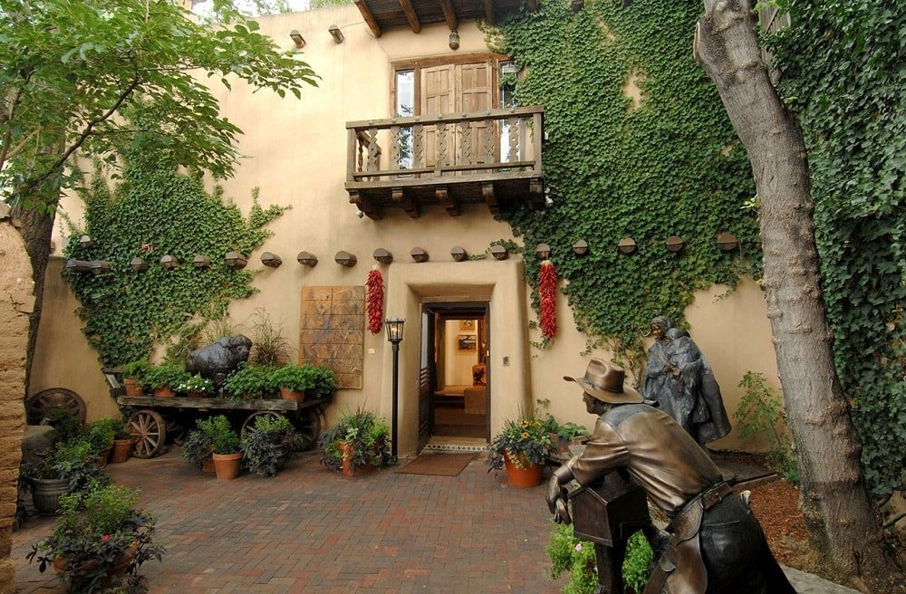 This is a view of the front of the house with beige walls adorned with creeping plants, statues and various plants that flank the entryway beneath the small wooden balcony.