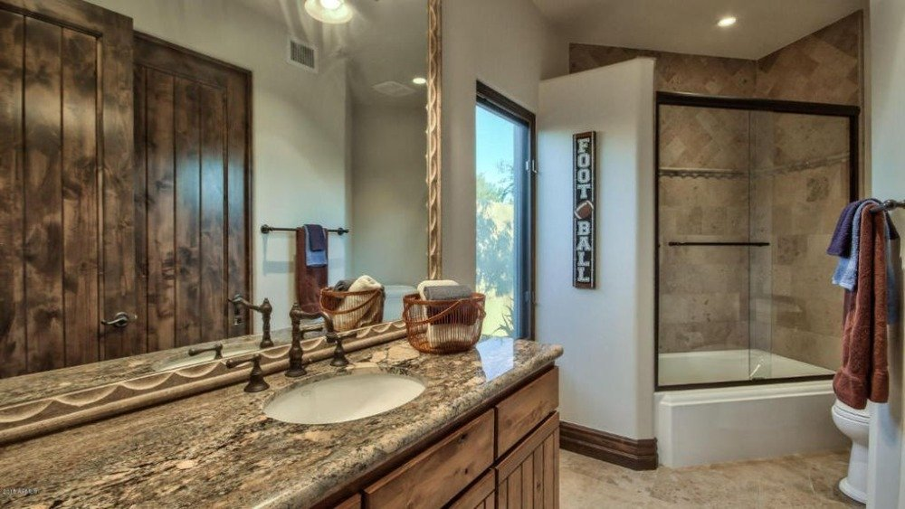 This bathroom features a rustic door along with a rustic sink counter. There's also a bathtub and shower combo. Image courtesy of Toptenrealestatedeals.com.