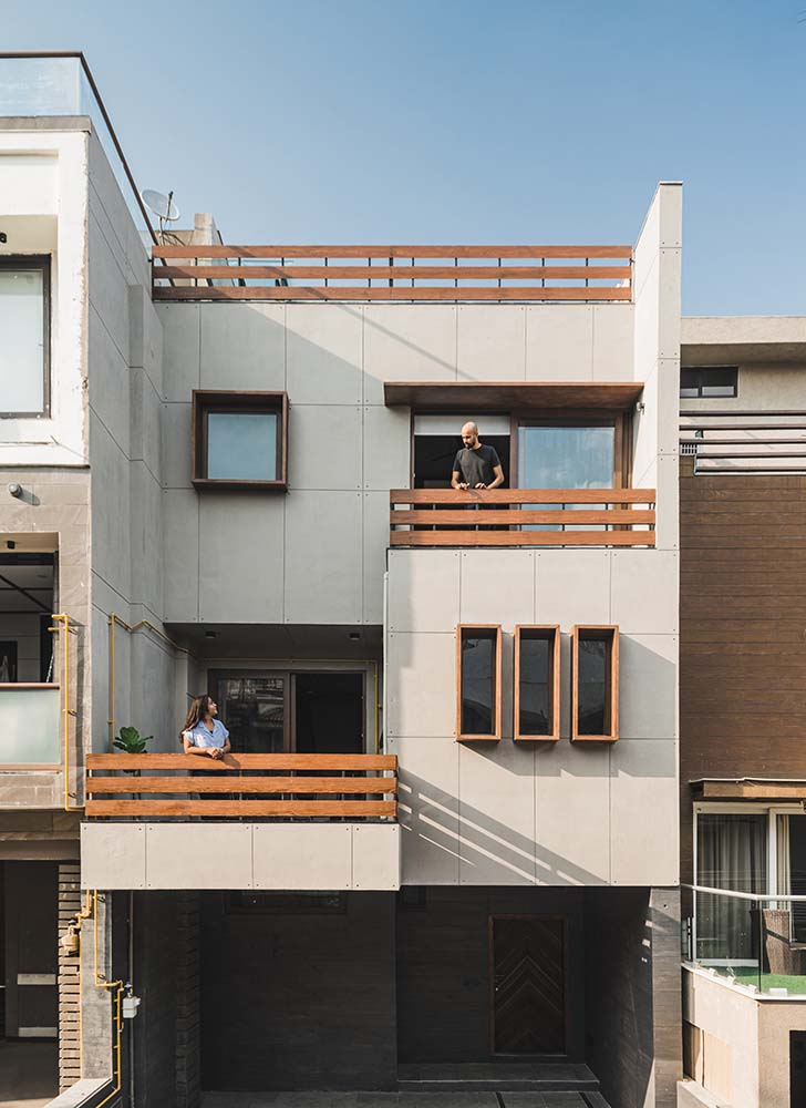 This is an exterior look at this suburban home that has a large car port and layers of balconies topped with a rooftop terrace.