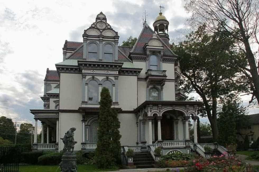 This is a view of the front of the large house that has unique architectural details, a tall tower, arched windows and a covered main entrance that is complemented by the lush landscaping.