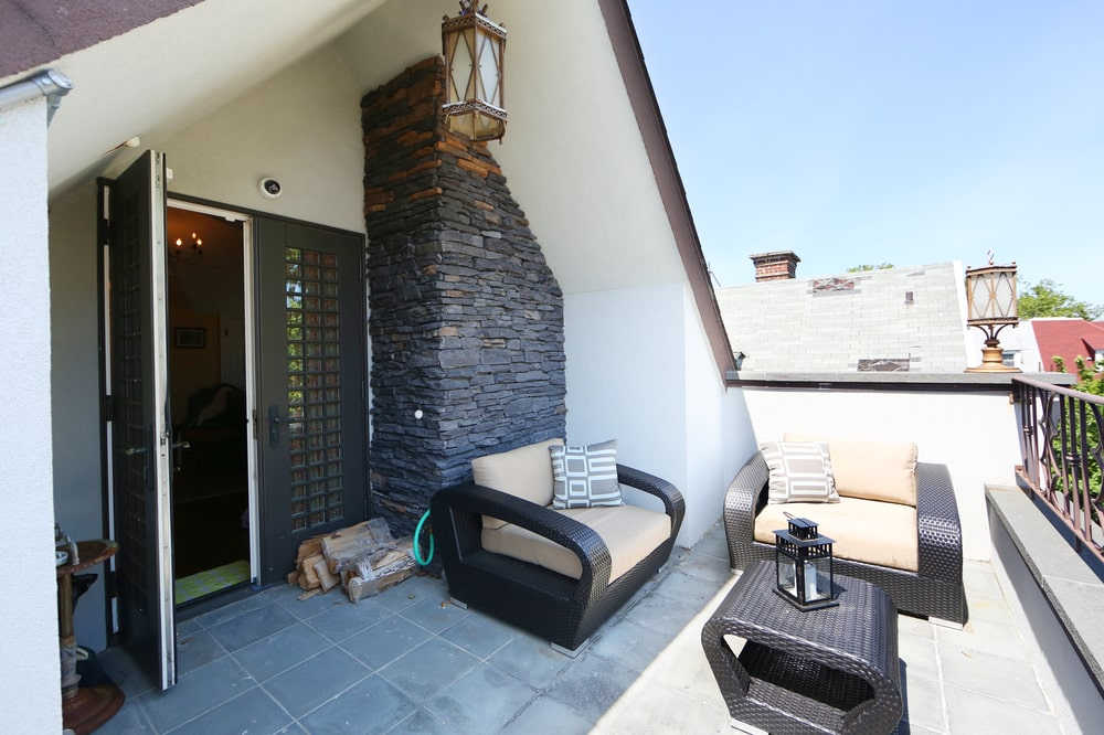 This is a look at the balcony fitted with a couple of armchairs and a coffee table with dark tones that match the stone wall by the door. Image courtesy of Toptenrealestatedeals.com.