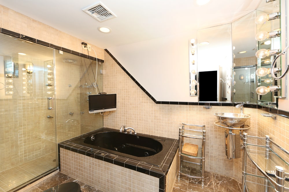 The bathroom has a black marble bathtub at the corner by the floating sink. Its dark tone makes it stand out against the surrounding beige tones. Image courtesy of Toptenrealestatedeals.com.