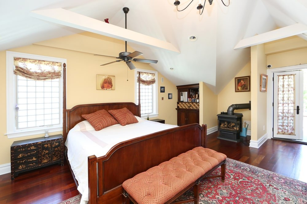 The bedroom has a large sleigh wooden bed that stands out against the white sheets and the beige walls. This is then topped with a white cathedral ceiling with exposed beams and ceiling fan. Image courtesy of Toptenrealestatedeals.com.