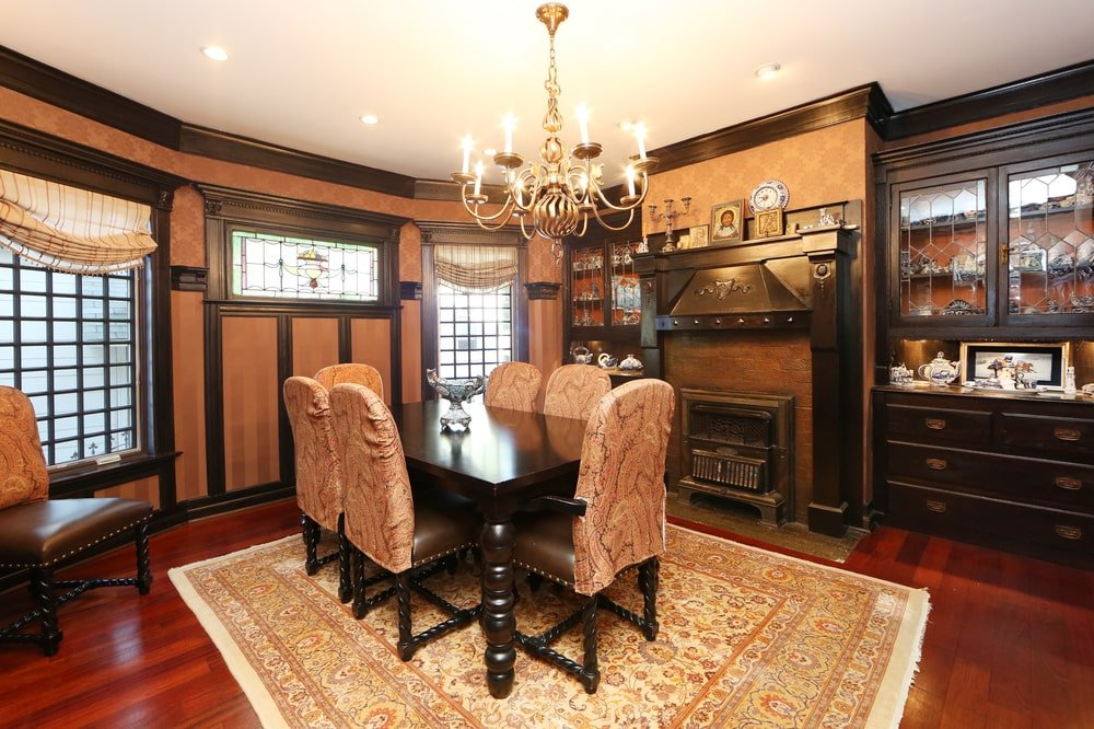 This is the formal dining room with a dark wooden dining table surrounded by matching beige chairs that go well with the beige area rug and walls with a fireplace. Image courtesy of Toptenrealestatedeals.com.