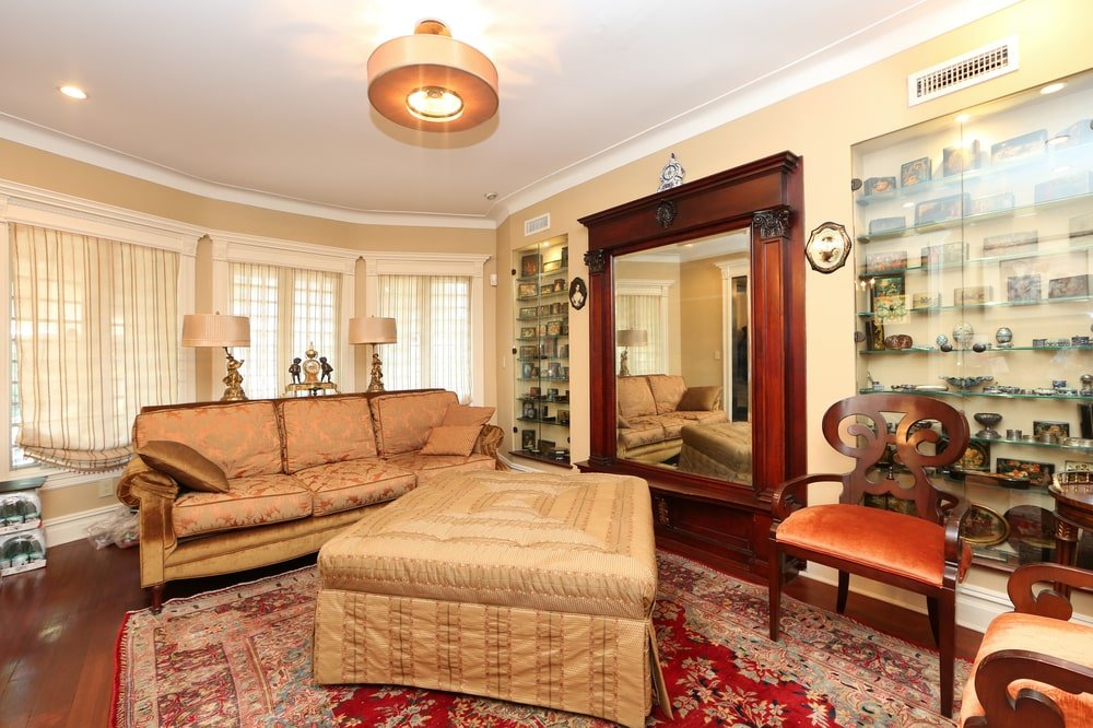 This is the living room with beige walls that match the beige cushions of the sofa and the coffee table on the red patterned area rug. Image courtesy of Toptenrealestatedeals.com.