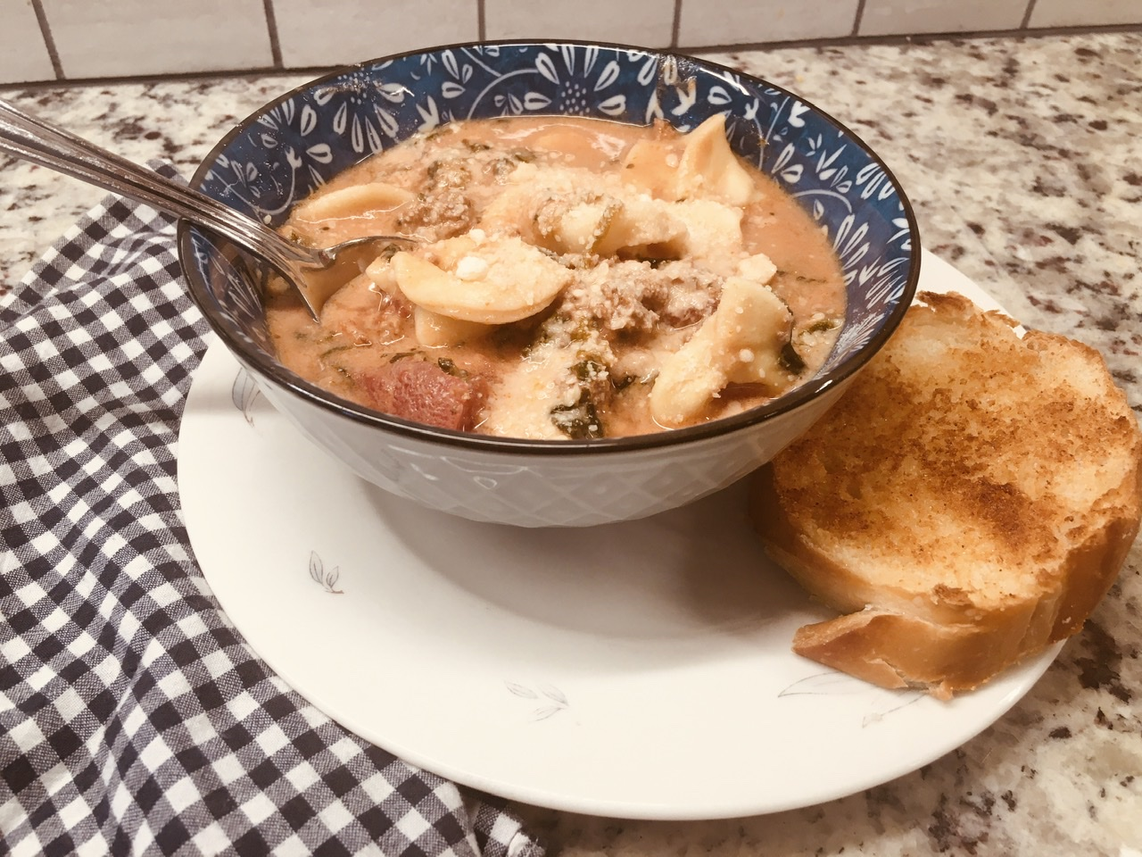 A serving of tortellini soup with a crusty bread on the side.