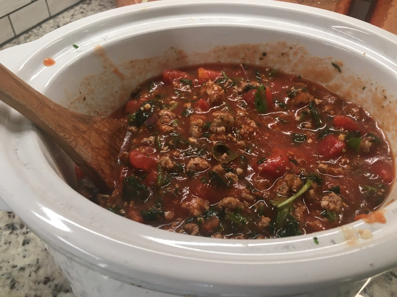 A mixture of Italian sausage, onion powder, garlic, basil, tomatoes, and tomato sauce in a slow cooker.