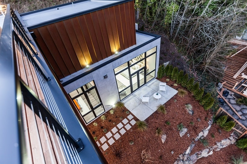 This is an aerial view of the backyard of the house just outside the glass walls. Here you can see that it has an outdoor patio with a concrete floor and concrete slab walkway. Image courtesy of Toptenrealestatedeals.com.