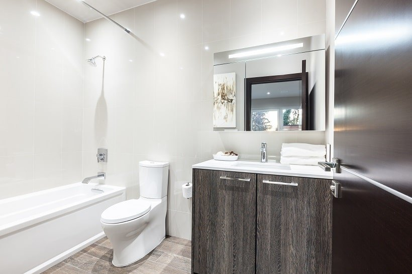 This bathroom has a dark vanity contrasted by the white countertop and toilet beside the bathtub on the far side. Image courtesy of Toptenrealestatedeals.com.