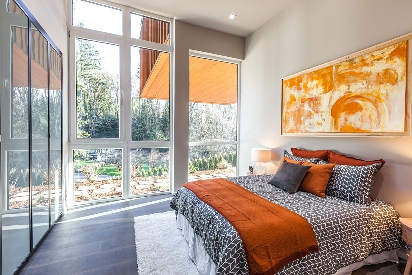 This bedroom has a colorful painting mounted above the headboard of the bed complemented by the large glass wall on the side that shows the landscape outside. Image courtesy of Toptenrealestatedeals.com.