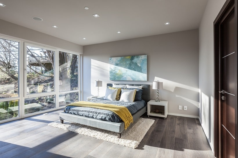 This bedroom has gray walls and ceiling to complement the bed that is adorned with a painting above the headboard and a glass wall on the side. Image courtesy of Toptenrealestatedeals.com.