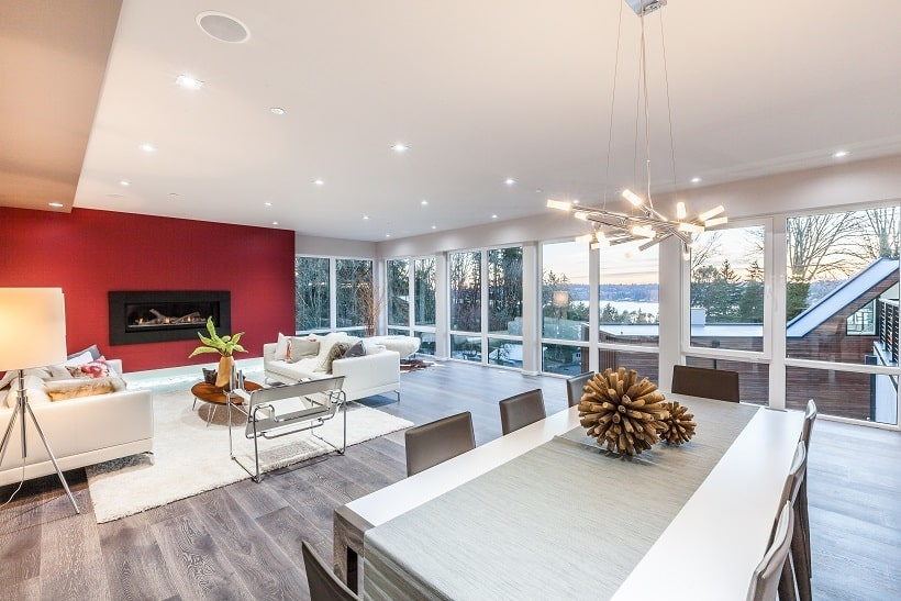 This is a look at the living room area from the vantage of the dining area. This shows the vast glass wall on the far side contrasted by the red wall of the living room. Image courtesy of Toptenrealestatedeals.com.