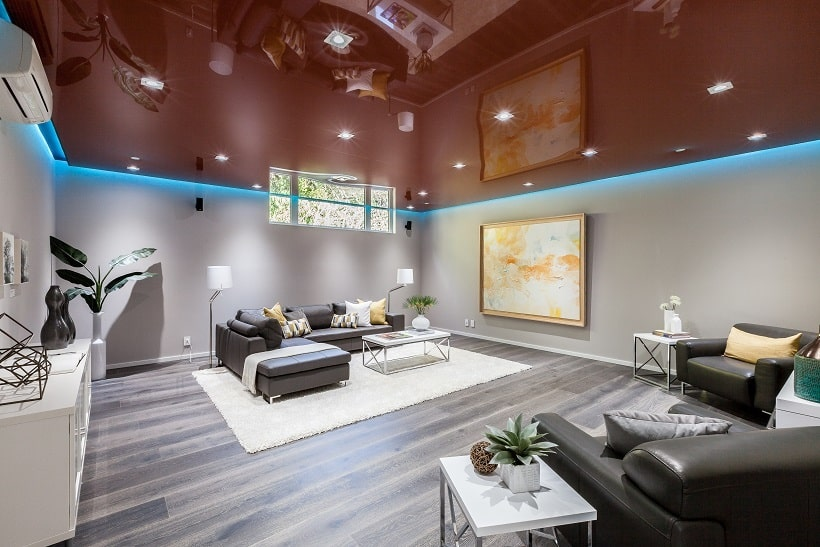 The spacious family room has a large black leather sectional sofa on the far side paired with a modern coffee table. These are then complemented by the shiny red ceiling. Image courtesy of Toptenrealestatedeals.com.