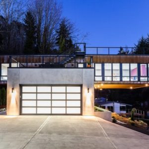 This is a front view of the contemporary-style home from the vantage of the concrete driveway leading to the garage door that matches the glass walls of the upper level. Image courtesy of Toptenrealestatedeals.com.
