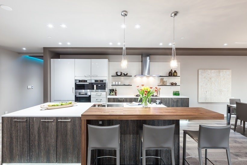 The kitchen has a large kitchen island that has a wooden extension on the side for the breakfast bar paired with gray stools. Image courtesy of Toptenrealestatedeals.com.