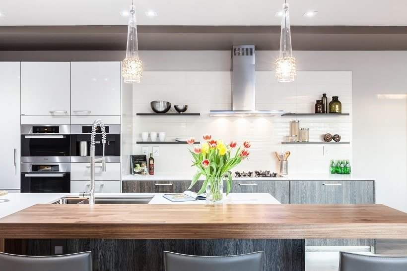 This angle of the kitchen shows the cooking area across from the kitchen island with a stainless steel vent. Image courtesy of Toptenrealestatedeals.com.