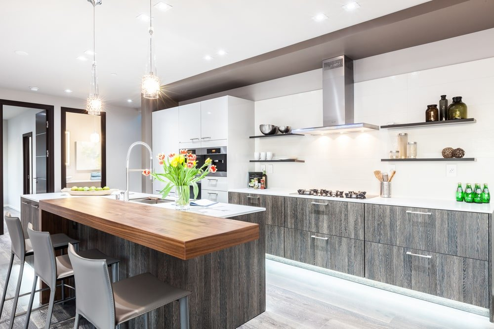 The kitchen has a tall white ceiling that has recessed lights and pendant lights hanging over the kitchen island. Image courtesy of Toptenrealestatedeals.com.