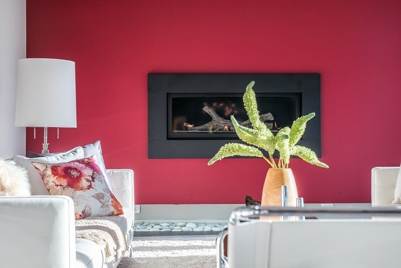 This is a close look at the living room with a red wall that houses the fireplace across from the sofa set with a coffee table. Image courtesy of Toptenrealestatedeals.com.