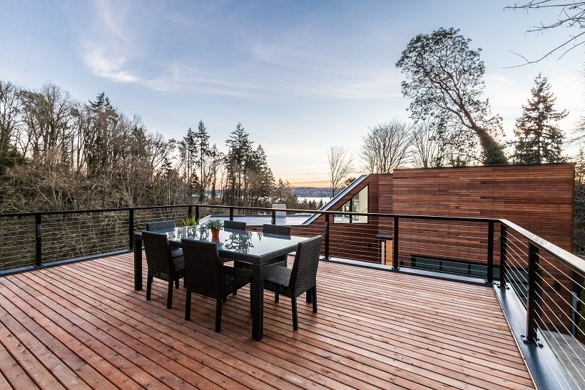This is the rooftop with a wooden deck floor fitted with an outdoor dining set with a black tone. Image courtesy of Toptenrealestatedeals.com.