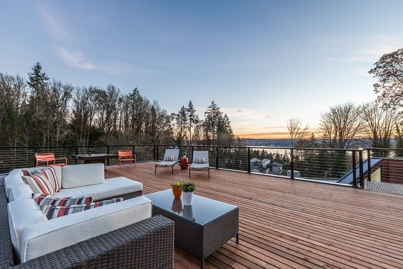 The rooftop also has an outdoor sofa set with a matching coffee table that stands out against the wooden deck floor. Image courtesy of Toptenrealestatedeals.com.