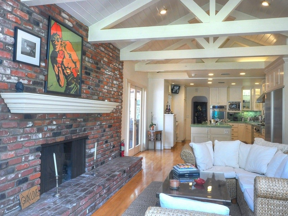 Across from the sofa is a large brick fireplace topped with a colorful painting. Image courtesy of Toptenrealestatedeals.com.