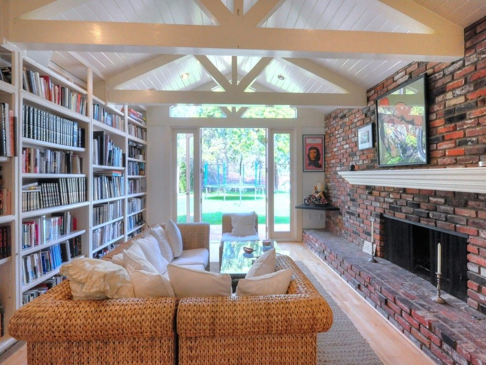 The family room has a white cathedral ceiling with exposed beams. It has an L-shaped sectional sofa with a wall of bookshelves behind. Image courtesy of Toptenrealestatedeals.com.