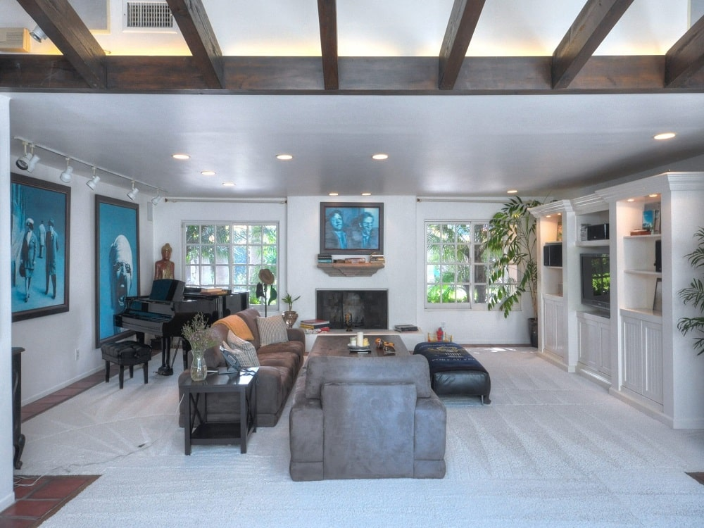 This other look at the living room showcases the fireplace on the far wall topped with a painting and flanked by two large windows. Image courtesy of Toptenrealestatedeals.com.