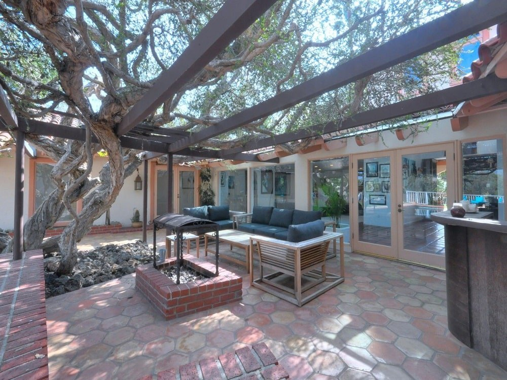 The patio just outside the glass doors has a sofa set and a firepit that can also double as a grilling station. These are then complemented by the tree and the trellises. Image courtesy of Toptenrealestatedeals.com.