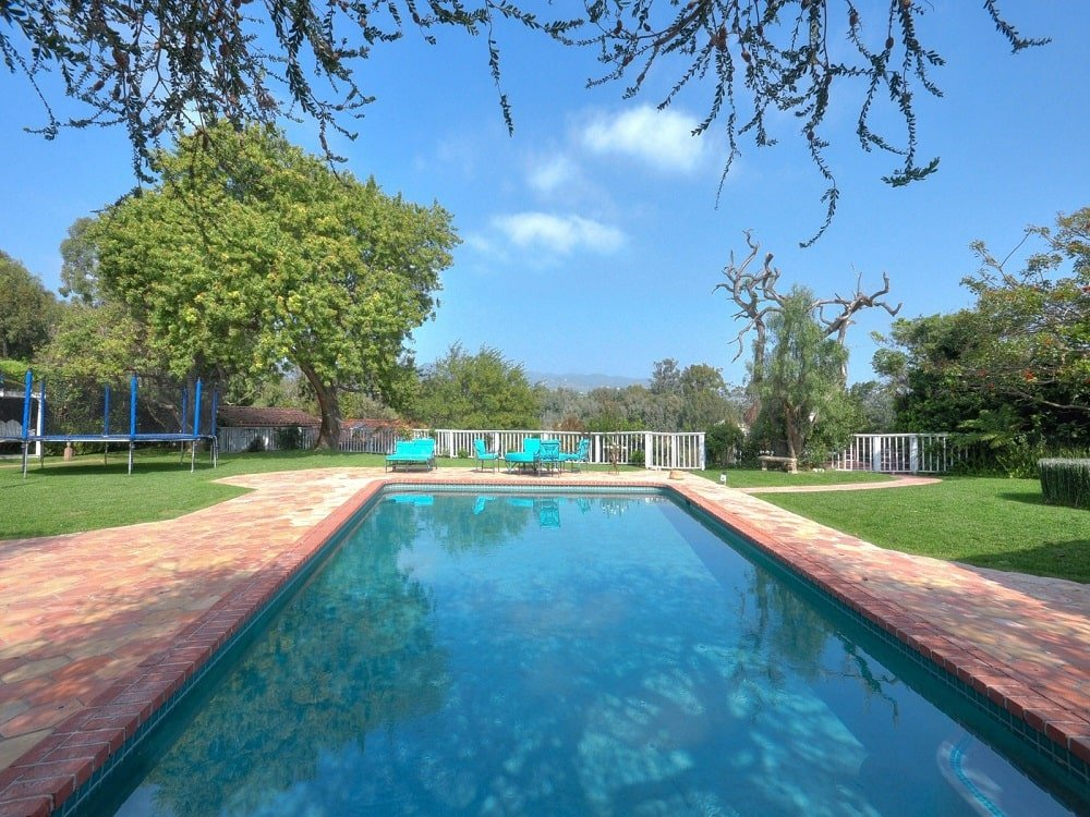 This is a close look at the pool from the vantage of the patio. Here you can see the terracotta brick walkways surrounding it and the various sitting areas on the far side. Image courtesy of Toptenrealestatedeals.com.