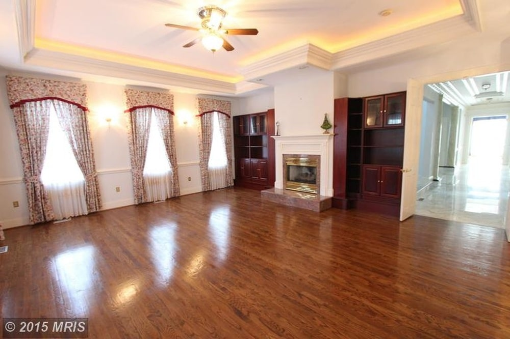 This family room has a wide hardwood flooring that matches well with the built-in wooden cabinets and shelves flanking the fireplace. Image courtesy of Toptenrealestatedeals.com.