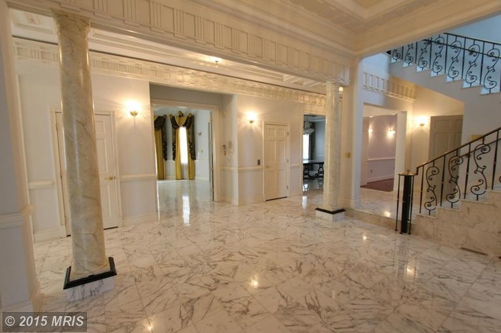 Upon entry of the house, you are welcomed by this foyer with a spacious white marble flooring adorned with pillars and warm lights on the walls. Image courtesy of Toptenrealestatedeals.com.