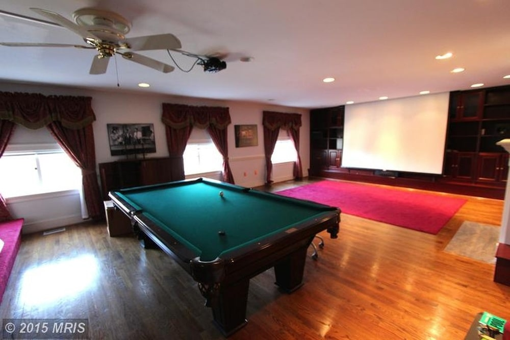 This is a look at the game room of the house fitted with a large pool table that matches the hardwood flooring. Image courtesy of Toptenrealestatedeals.com.