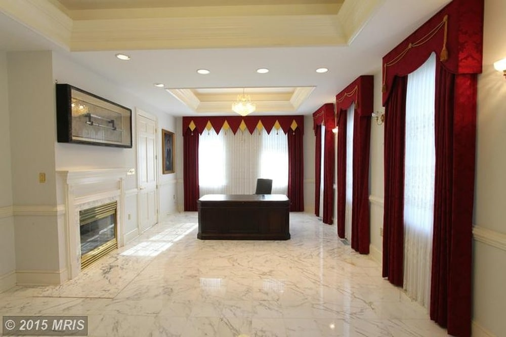 This is the spacious office with a white marble flooring that makes the dark wooden desk stand out. Image courtesy of Toptenrealestatedeals.com.