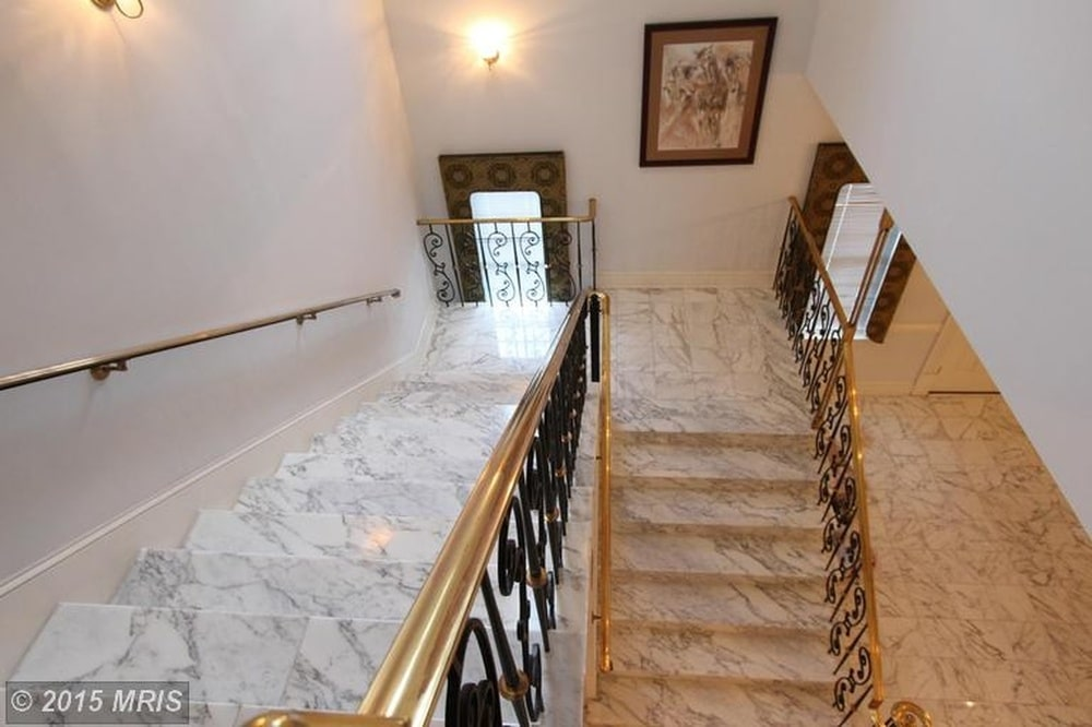 This is a look down the marble steps of the staircase adorned with intricate wrought-iron railings on the side. Image courtesy of Toptenrealestatedeals.com.