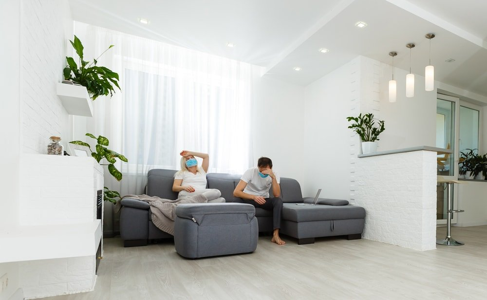 A couple wearing face masks sits on a gray sofa in a modern living room.