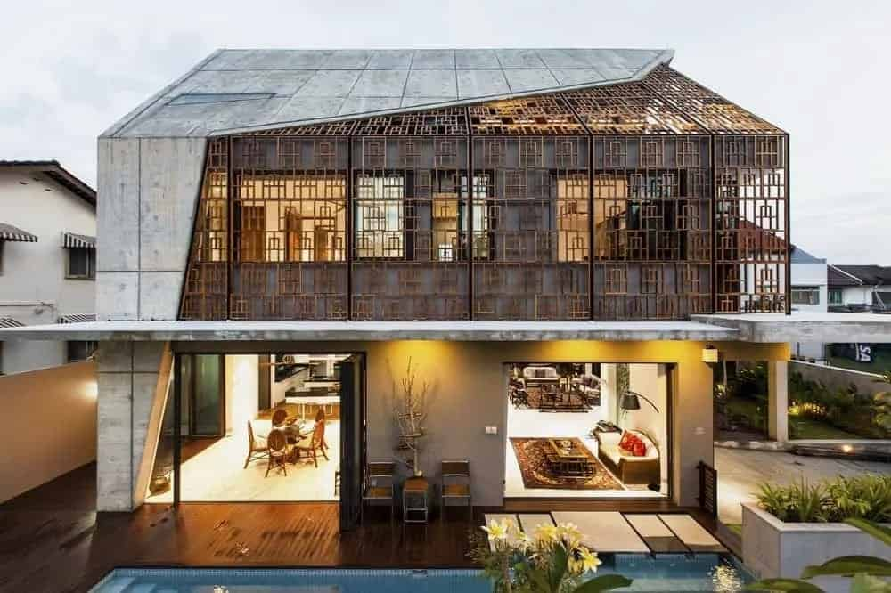 This aerial view of the house showcases the open walls of the lower level to access the outdoor areas and the second level that is adorned with detailed panels that also gives a glimpse of the warm interiors.