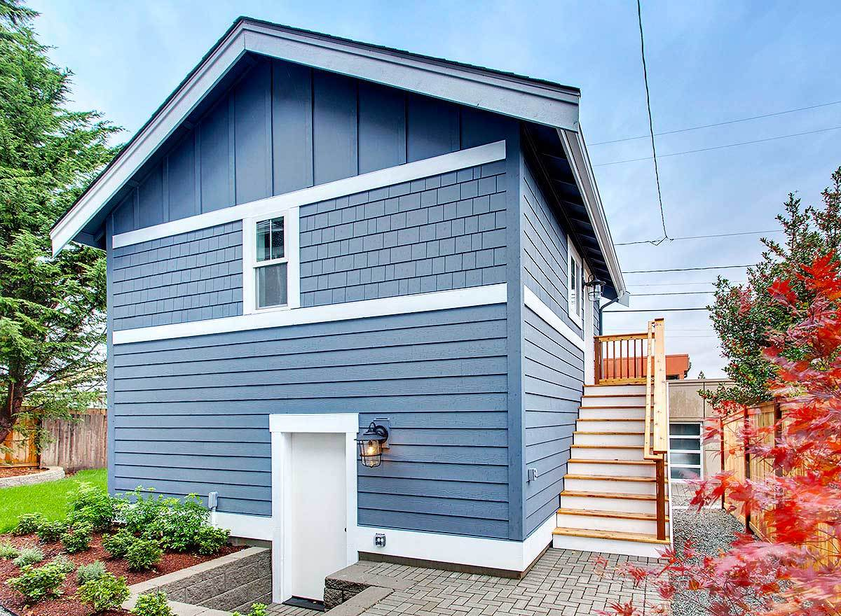Rear exterior view with a white door leading to the garage and a wooden staircase that brings you to the main living space.