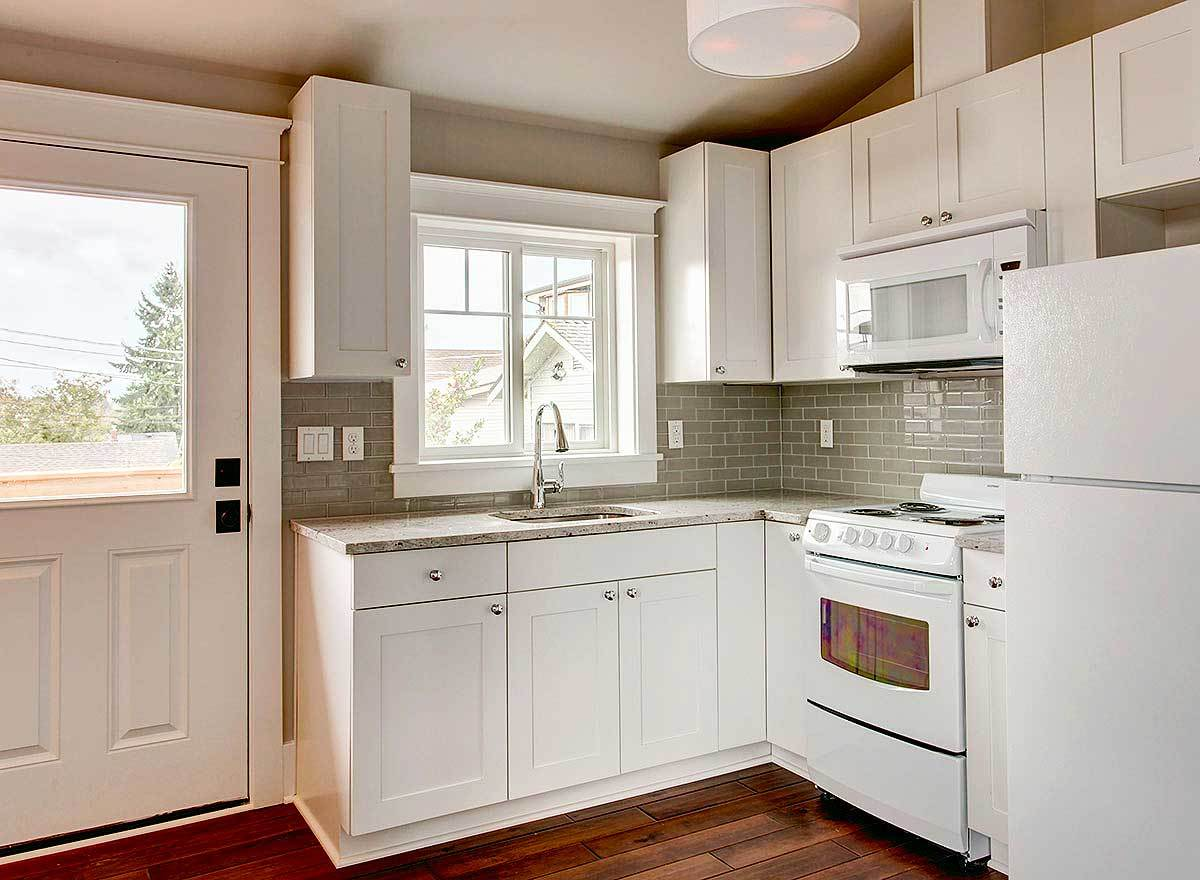 The kitchen has white appliances, custom cabinets, and a gray subway tile backsplash.