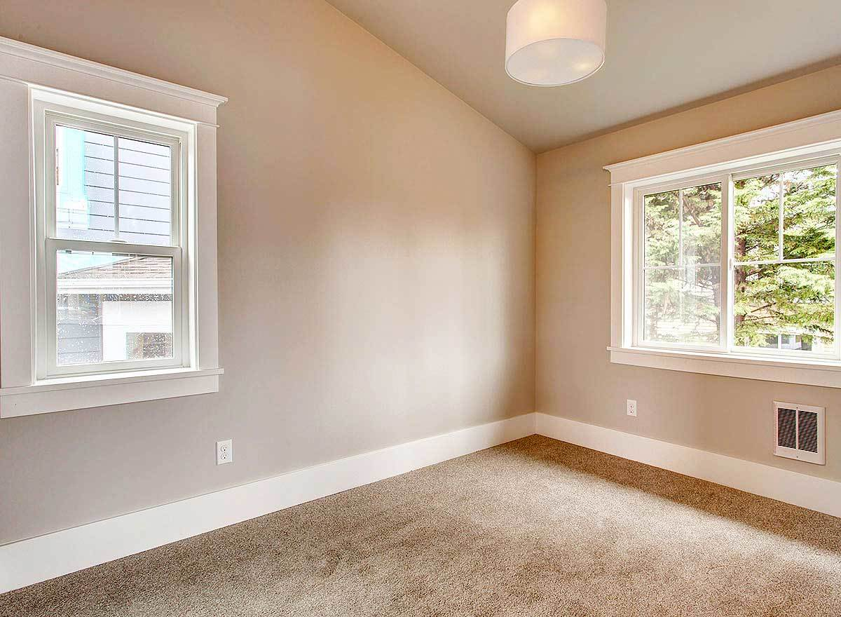 Here is the bedroom with carpet flooring, beige walls, and vaulted ceiling mounted with a drum chandelier.